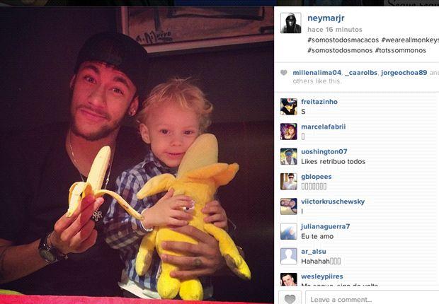 Neymar si mangia la banana con il figlio in braccio